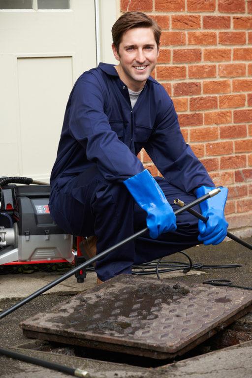 A man cleaning a main drain