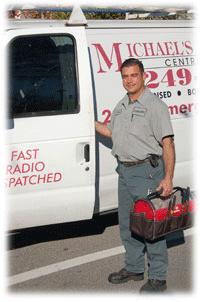 Service man standing by Michael's Plumbing van
