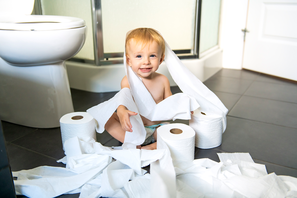 A toddler sitting among several unwound rolls of toilet paper