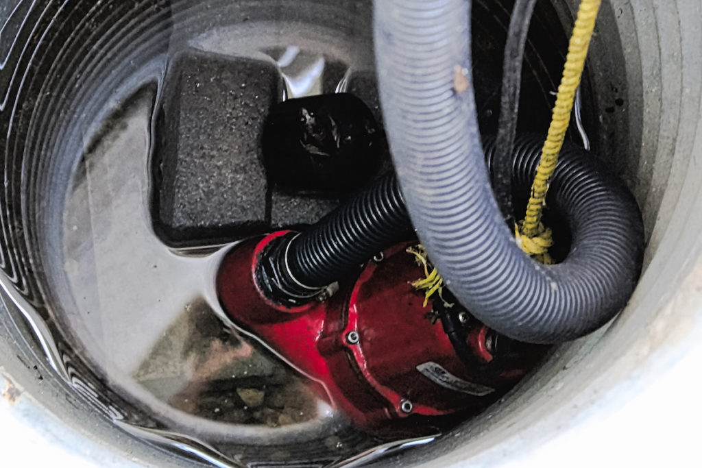 A sump pump with some water around it.