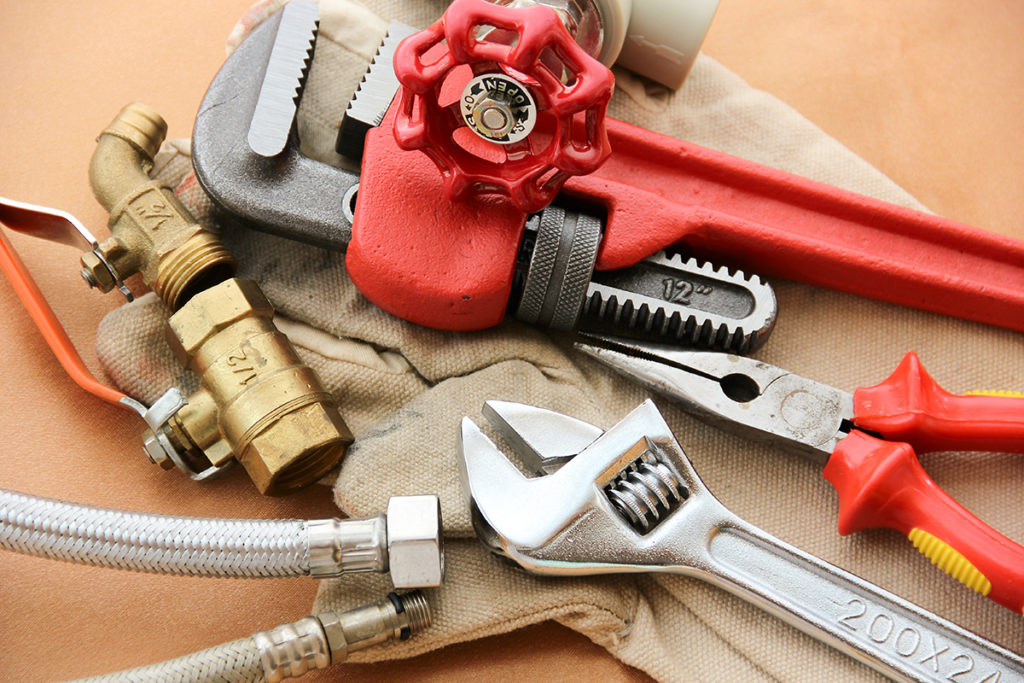 An adjustable wrench, a pipe wrench, a pair of pliers, and a pipe