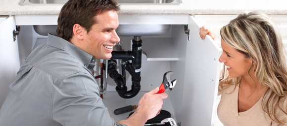 Service man speaking with woman while fixing sink