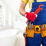 Torso of a plumber wearing overalls and a tool belt